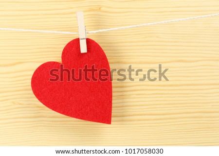 red love heart on clothesline against wood #1017058030