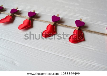 Red love hearts fastened on a decorative clothespin. #1058899499