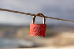 Red love padlock attached to steel wire. Rusty lock with heart shape carved hanging on railing outdoors. Valentines day, unity, memory concepts