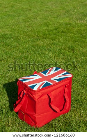 red lunch bag with the union flag (United Kingdom) on the grass field (copy-space available) - stock photo
