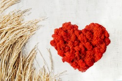 red lush heart of decorative real moss on light table with bouquet of dried flowers, eco-friendly gifts and decor, top view, selective focus