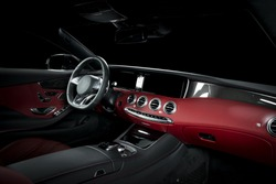 Red luxury car Interior - steering wheel, shift lever and dashboard. Clipping path for windows included