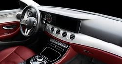 Red luxury modern car Interior. Steering wheel, shift lever and dashboard. Detail of modern car interior. Automatic gear stick. Part of leather seats with stitching in expensive car