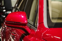 Red luxury SUV car rear view mirror close up view