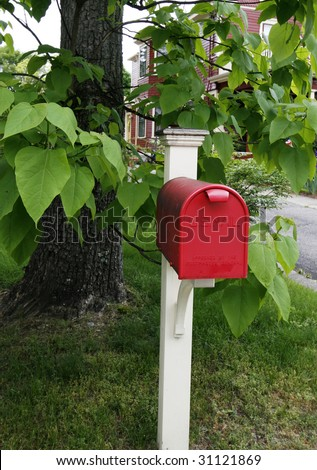 red mailbox in front of tree - stock photo