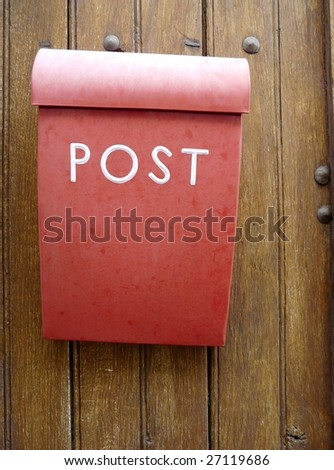 Red mailbox or postbox on a wooden door