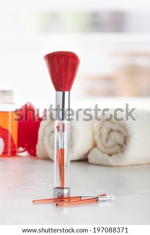 Red makeup brush set placed on a makeup table.