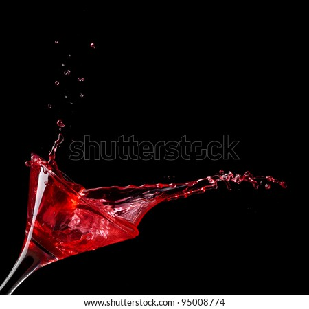 red martini cocktail splashing into glass on black background