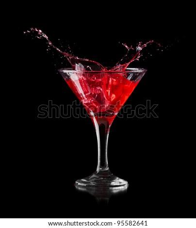 red martini cocktail splashing into glass on black background