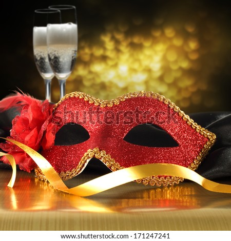red mask and gold ribbon and champagne