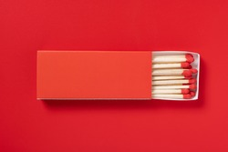 red matchbox and red match sticks on a red background