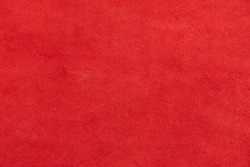Red matte background of suede fabric, closeup. Velvet texture of seamless leather. Felt material macro. Red suede texture. Fabric, leather, material for designers.