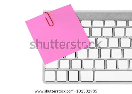Red memo and paper clip on computer keyboard on the white background