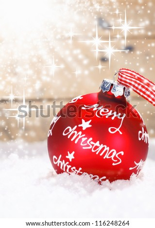 Red Merry Christmas bauble tied with a fresh red and white checked ribbon nestling in winter snow with twinkling stars of moisture lit by sun flare with copysapce