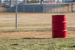 Red metal barrel with chain link and ball field.  Green grass in the foreground with grey steel fence.  Country ball field in background.  Solitary trash can.