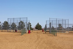 Red metal barrels with chain link and ball field.  Tan dirt in the foreground with grey steel fence.  Country ball field in background.