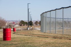Red metal barrels with chain link, bokeh light poles and ball field.  Green grass in the foreground with grey steel fence.  Country ball field in background.