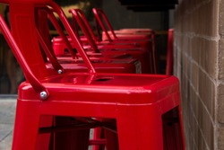 Red, metal chair. Industrial style, tall stool/seat for sitting.
