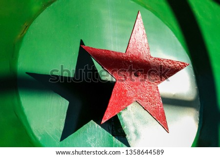 Red metal five-pointed star on a green background