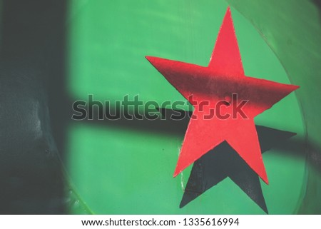 Red metal five-pointed star on a green background. Soviet national political symbol. Soviet Union
