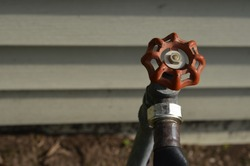 Red Metal Outside Faucet Hose Bibb Round Wheel Handle with a cream house siding in the background