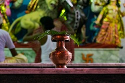 Red metallic lota with mango leaves on top in front of devi durga during durgapuja