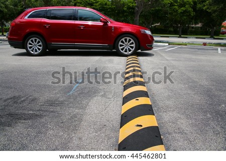Red Minivan Driving Up to and Just Connecting with Yellow and Black Striped Speed Bump in Parking Lot with Diagonal Striped Spaces and Trees in the Background, Mid-Day #445462801