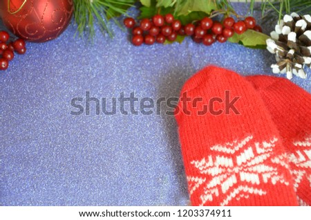 red mittens and christmas decoration on wooden background #1203374911