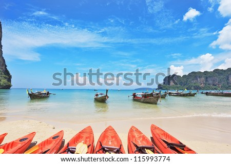 Red modern boats- canoes and boats classic Longtail awaiting tourists. Thailand, the southern islands
