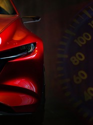 Red modern car headlights on car instrument panel background