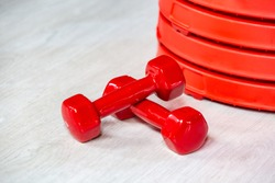 Red modern dumbbells and pancakes for dumbbells in the foreground on a wooden floor