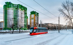 Red modern tram on the street in Izhevsk, Russia. New trams for Russian cities.