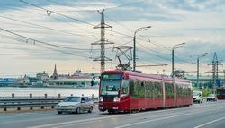 Red modern tram on the street in Kazan, Russia. Tram in front of the Kazan Kremlin.