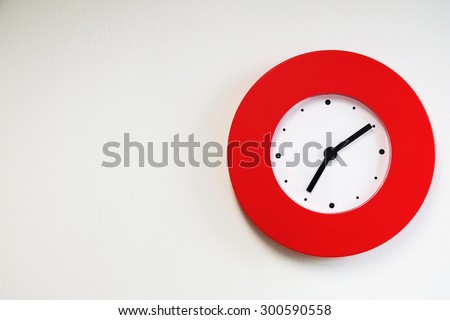 Red modern wall clock on white concrete wall #300590558