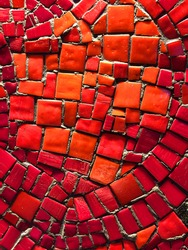 Red mosaic tiles of irregular sizes arranged in a background motif. Space for text.