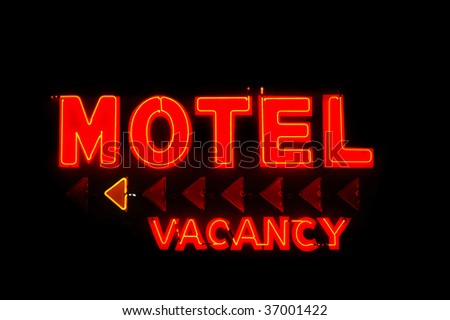 Red motel and vacancy neon sign with arrows isolated on black background