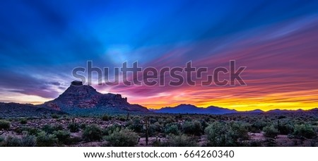 Red Mountain Blur - a time exposure renders wispy, mysterious clouds in a colors thanks to the setting sun.  The foreground is a vibrant desert landscape highlighted by Mesa, AZ' Red Mountain.   #664260340