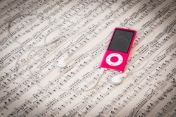 Red Mp3 music player and earphones on a music sheet background with song notes