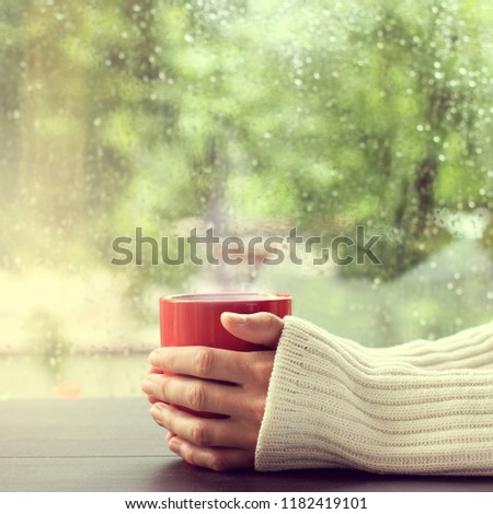 red mug of hot drink in hand on the background of a wet window / warming atmosphere after a rain