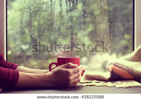 red mug of hot drink, when behind a window is rain / cozy home atmosphere