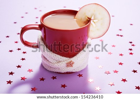 red mug of tea over lilac background with red stars