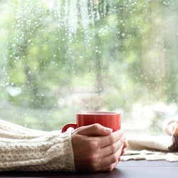 red mug with a hot drink in the hands of a person dressed in a warm sweater near the window / time to drink a warm drink