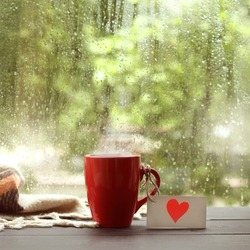 red mug with a note depicting a heart, on the table by the window with drops after rain. warming drink with a love message
