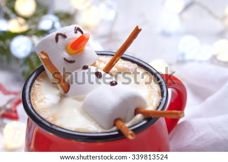 Red mug with hot chocolate with melted marshmallow snowman - Shutterstock ID 339813524