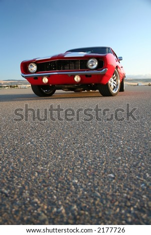 red muscle car camaro and asphalt at ground level
