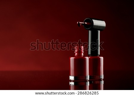 red nail polish on glass table with red background