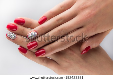 red nails with crystals and hands isolated on white background