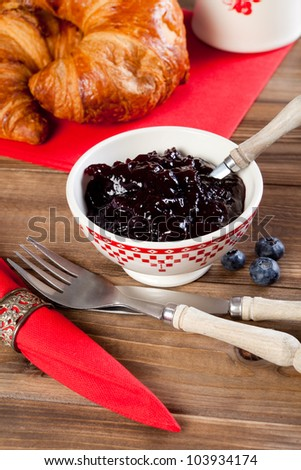 Red napkins, fruity jam and croissants on a wooden breakfast table