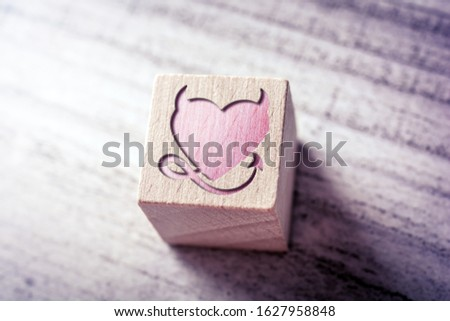 Red Naugthy Heart With Devil Horns And Tail Engraved On A Wooden Block On A Table