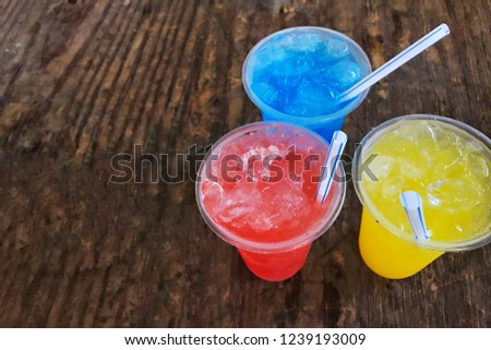 Red Nectar Blue Nectar Yellow Nectar is all in a plastic glass. Put on a wooden table